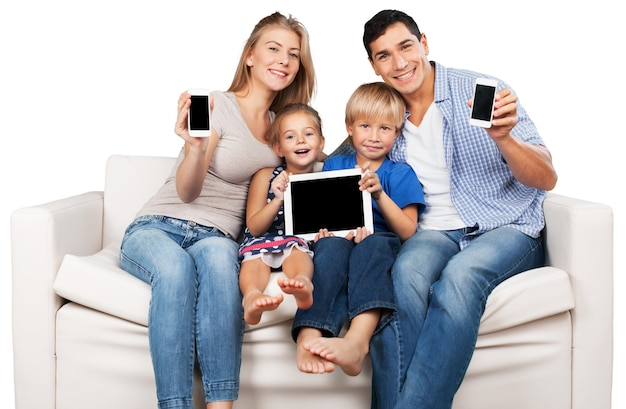 Piękna uśmiechnięta rodzina siedząca przy kanapie z elektronicznymi gadżetami w domu
