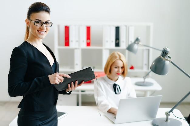 Piękna uśmiechnięta rozochocona dziewczyna przy miejsca pracy spojrzeniem
