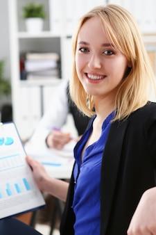 Piękna uśmiechnięta rozochocona dziewczyna przy miejscem pracy