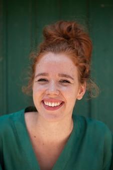 Piękna uśmiechnięta rudzielec kobieta patrzeje kamerę