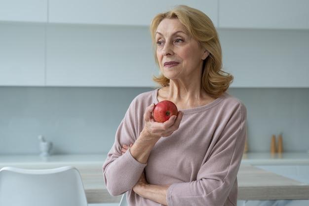 Piękna, uśmiechnięta starsza kobieta, trzymająca w dłoniach czerwone jabłko, stojąca w kuchni