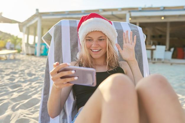 Piękna uśmiechnięta szczęśliwa nastolatka w kapeluszu świętego mikołaja siedzi w leżaku na plaży ze smartfonem