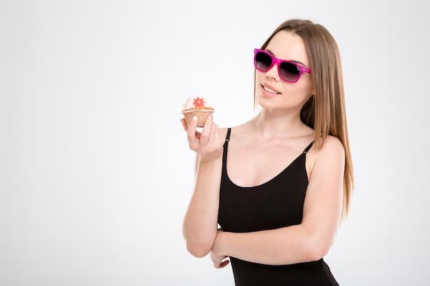 Piękna uśmiechnięta szczęśliwa treść radosna atrakcyjna dziewczyna w różowych okularach przeciwsłonecznych trzymająca w dłoniach babeczkę