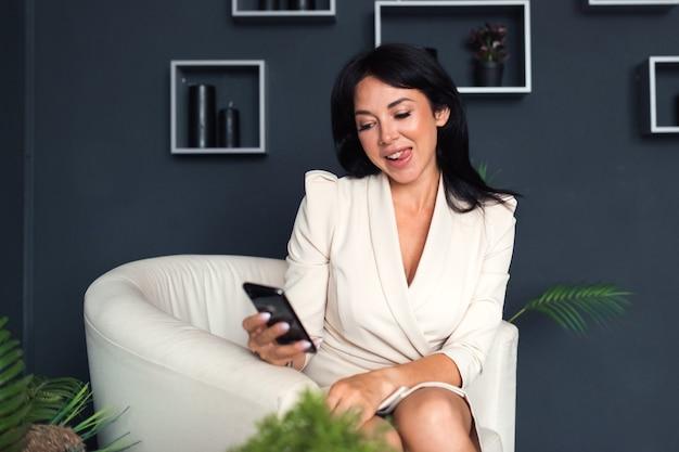 Piękna uśmiechnięta twarz kobieta brunetka pozuje ze smartfonem robiąc miny w mediach społecznościowych