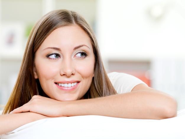 Piękna uśmiechnięta twarz kobiety odwracając wzrok - w pomieszczeniu