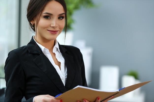 Piękna uśmiechnięta urzędnik dziewczyna jest ubranym kostiumu chwyta notatnika