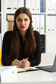 Piękna uśmiechnięta urzędnik dziewczyna w miejscu pracy rozmawiać z gościem