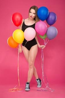 Piękna uwodzicielska atrakcyjna młoda dama w czarnym trykocie i trampkach pozuje z kolorowymi balonami na różowej ścianie