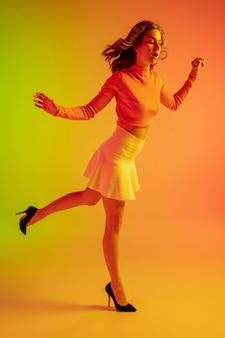Piękna uwodzicielska dziewczyna w modnym romantycznym stroju na jasnym gradientowym zielonopomarańczowym