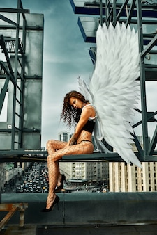 Piękna uwodzicielska kobieta anioł ubrana w bieliznę przykucnięta na dachu w wielkim mieście z wiatrem w skrzydłach nad zachmurzonym niebem