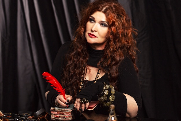 Piękna w wieku rudowłosa wróżka wykonuje magiczny rytuał.