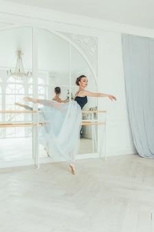 Piękna wdzięczna balerina ćwiczy pozycje baletowe w niebieskiej spódniczce tutu w pobliżu dużego lustra w białym świetle