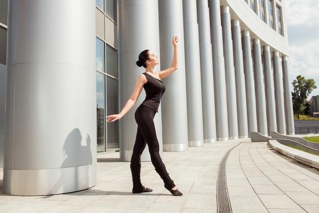 Piękna wdzięczna baletnica tańczy przed budynkiem