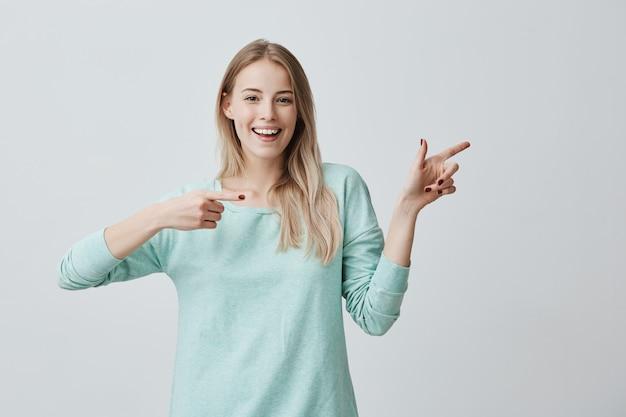 Piękna wesoła blondynka uśmiecha się szeroko i wskazuje palcami wskazującymi, pokazując coś interesującego i ekscytującego