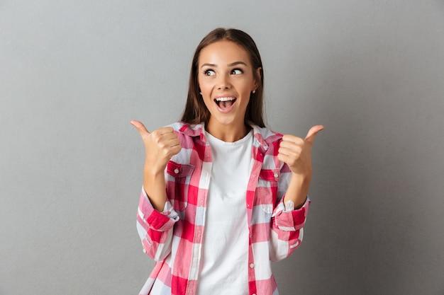 Piękna wesoła brunetka kobieta w kraciaste koszule, pokazując kciuk do góry gest, odwracając wzrok