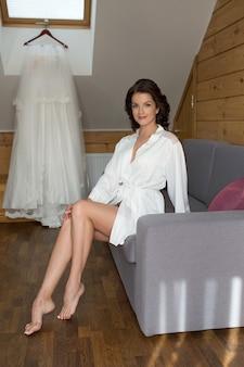 Piękna wesoła brunetka panna młoda w białej jedwabnej szacie przygotowuje się do ślubu