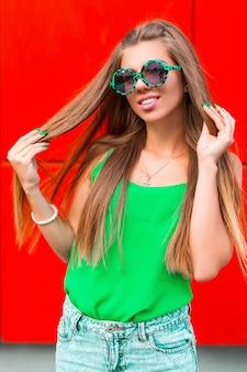 Piękna wesoła dziewczyna w okularach przeciwsłonecznych na jaskrawej czerwieni