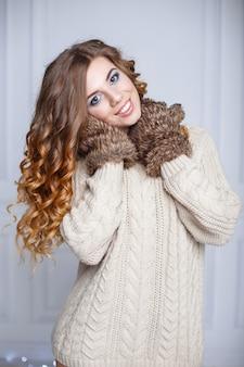 Piękna wesoła dziewczyna z niesamowitym uśmiechem w ciepłym swetrze i rękawiczkach