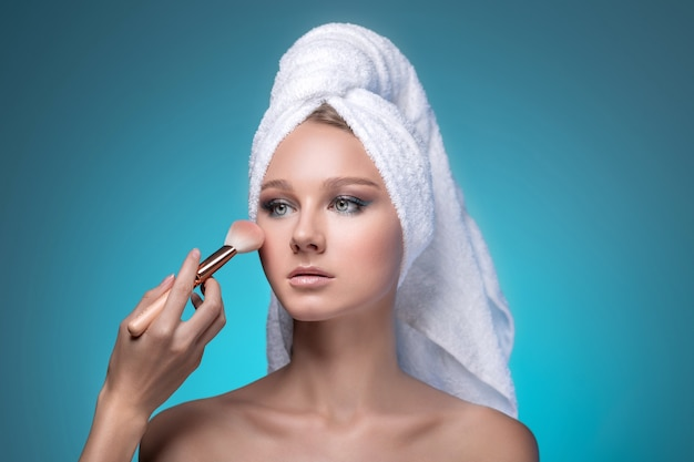 Piękna wesoła kobieta robi makijaż. wizażystka ręką dotykając twarzy pędzlem.