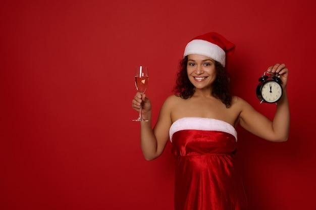 Piękna, wesoła kobieta w stroju karnawałowym santa trzyma flet szampana z winem musującym i pudełko, uśmiech toothy uśmiech pozowanie na czerwonym tle, miejsce na reklamę. boże narodzenie, szczęśliwego nowego roku
