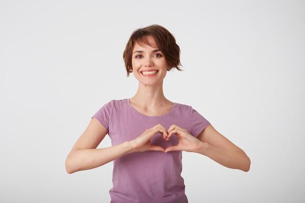 Piękna wesoła krótkowłosa dama w pustej koszulce, pokazuje gest w kształcie serca, nosi casualową koszulkę, ciesząc się, stoi na białym tle. symbol miłości, romantyczny nastrój.