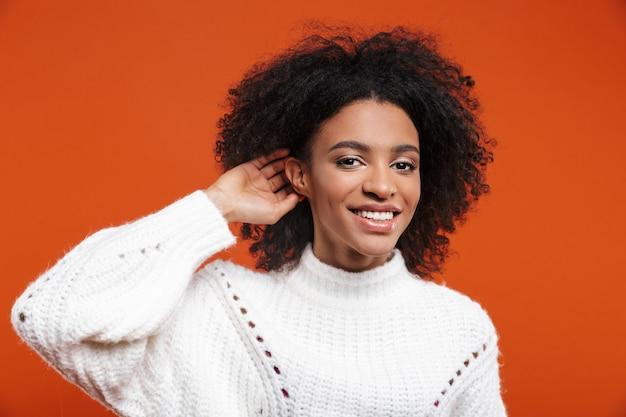 Piękna, wesoła młoda afrykańska kobieta ubrana w sweter stojący na czerwonej ścianie, próbująca usłyszeć plotki