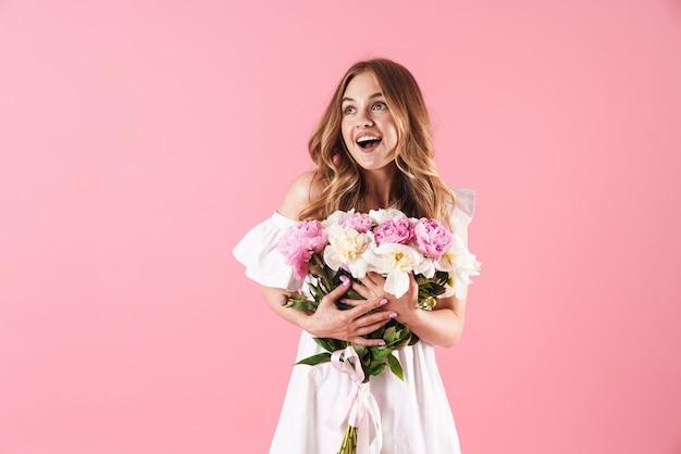 Piękna wesoła młoda blondynka na sobie letnią sukienkę stojącą na białym tle nad różową ścianą, trzymając bukiet piwonii