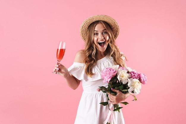 Piękna wesoła młoda blondynka ubrana w letnią sukienkę stojącą na białym tle nad różową ścianą, świętującą przy lampce wina i bukiet kwiatów