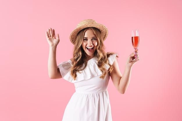 Piękna wesoła młoda blondynka ubrana w letnią sukienkę stojącą na białym tle nad różową ścianą, świętującą przy lampce wina