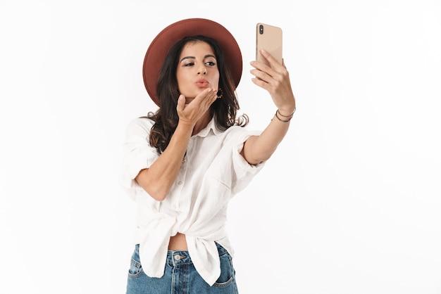 Piękna, wesoła młoda brunetka ubrana w zwykłe ubranie, stojąca na białym tle nad białą ścianą, biorąca selfie, wysyłająca buziaka