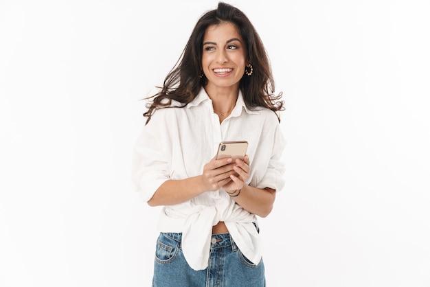 Piękna, wesoła młoda brunetka, ubrana w zwykłe ubranie, stojąca na białym tle nad białą ścianą, przy użyciu telefonu komórkowego