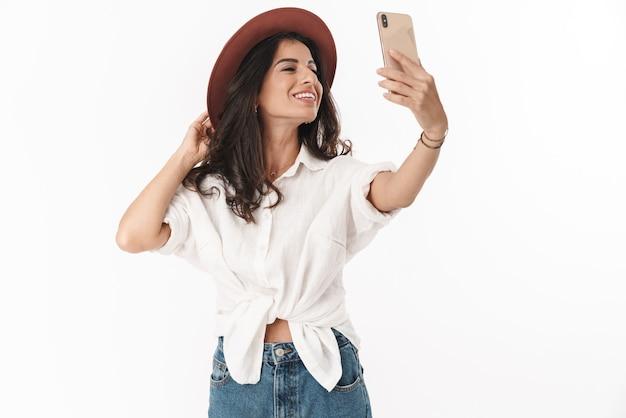 Piękna, wesoła młoda brunetka w stroju casual stojąca na białym tle nad białą ścianą, biorąc selfie