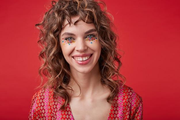 Piękna wesoła młoda dama z kręconymi włosami i świątecznym makijażem stojąca w pstrokatym wzorzystym topie, patrząc z radosnym szerokim uśmiechem