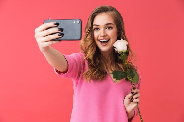 Piękna, wesoła młoda dziewczyna w zwykłych ubraniach, stojąca na białym tle nad różową ścianą, robiąca selfie, trzymająca różę