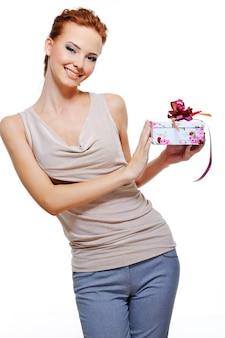 Piękna wesoła młoda kobieta trzyma małe pudełko na prezent