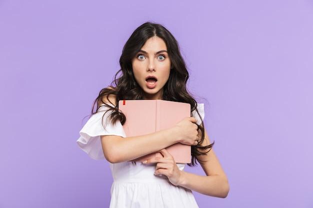 Piękna, wesoła młoda kobieta w letnim stroju, stojąca na białym tle nad fioletową ścianą, robiąca notatki w swoim pamiętniku