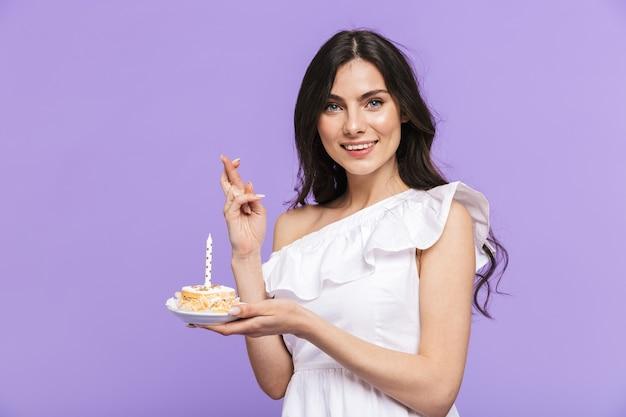 Piękna wesoła młoda kobieta w letnim stroju stojąca na białym tle nad fioletową ścianą, świętująca urodziny ciastem