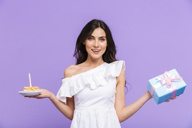 Piękna wesoła młoda kobieta w letnim stroju stojąca na białym tle nad fioletową ścianą, świętująca urodziny z ciastem, trzymająca pudełko