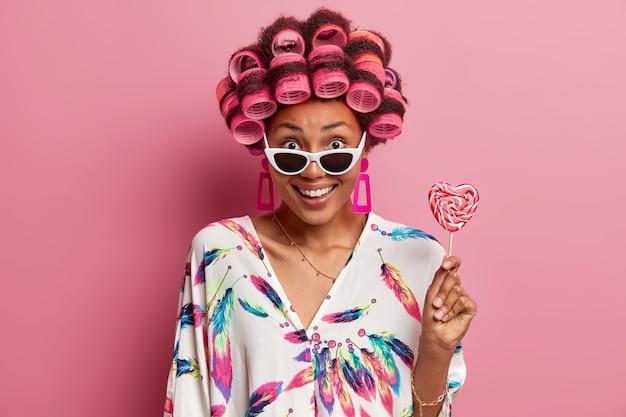 Piękna wesoła młoda kobieta w modnych okularach przeciwsłonecznych, nosi lokówki, robi fryzurę, ubrana w suknię domową, trzyma lizaka. szczęśliwa etniczna dama pozuje dla fotografa z pysznymi cukierkami
