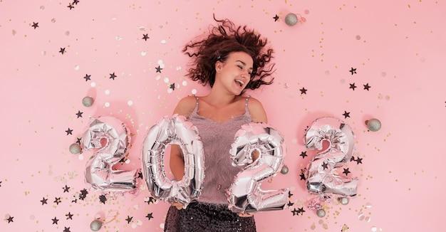 Piękna wesoła odświętnie ubrana brunetka dziewczyna z kręconymi włosami na różowym tle ze srebrnymi balonami z numerów 2022, koncepcja party nowy rok.