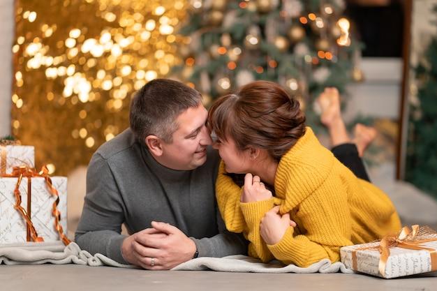 Piękna wesoła para wita święta bożego narodzenia w przytulnej domowej atmosferze