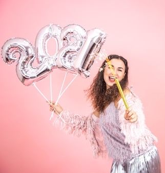 Piękna wesoła świątecznie ubrana brunetka dziewczyna z kręconymi włosami, pozowanie na tle różowego studia ze srebrnymi balonami na koncepcję nowego roku