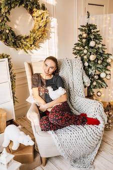 Piękna wesoła szczęśliwa młoda dziewczyna w piżamie z prezentami świątecznymi na kanapie na tle drzewa noworocznego w domu