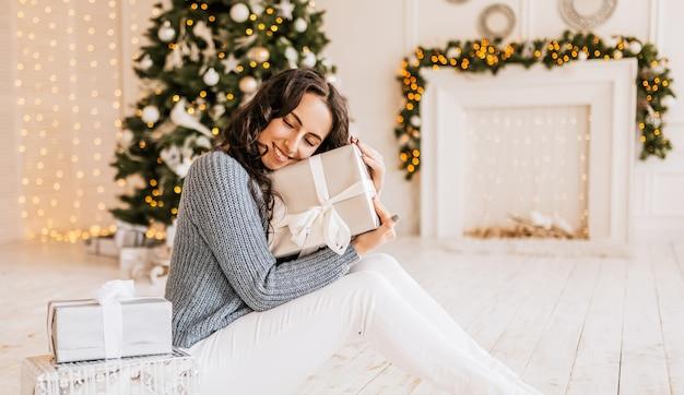 Piękna wesoła szczęśliwa młoda dziewczyna z prezentami świątecznymi na tle drzewa nowego roku w domu