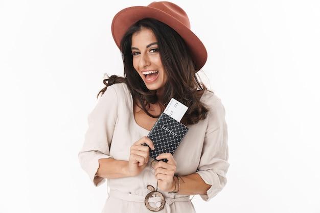 Piękna wesoła urocza młoda brunetka ubrana w letnią sukienkę i kapelusz stojący na białym tle nad białą ścianą, pokazująca paszport z biletami lotniczymi