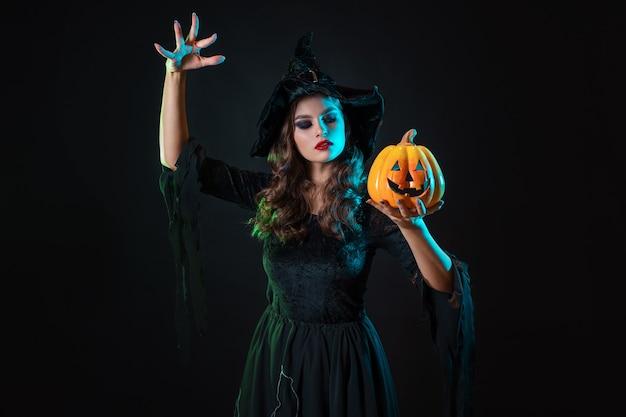 Piękna wiedźma w kapeluszu rzuca zaklęcie nad dynią jackolantern