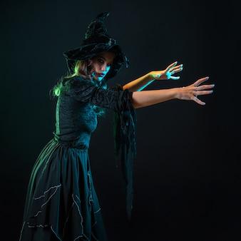 Piękna wiedźma w kapeluszu sprawia, że zaklęcie halloween party czarownice sabat