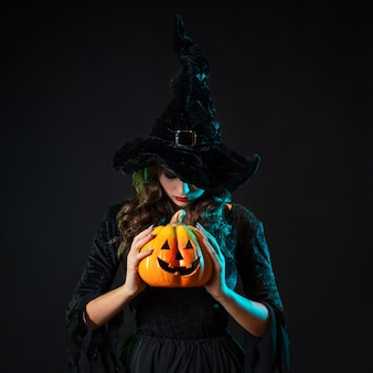 Piękna wiedźma w szpiczastym kapeluszu trzyma w dłoniach dynię z płonącymi oczami