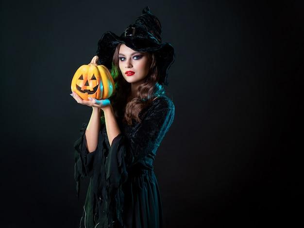 Piękna wiedźma w szpiczastym kapeluszu trzymająca dynię ze śmiejącą się twarzą