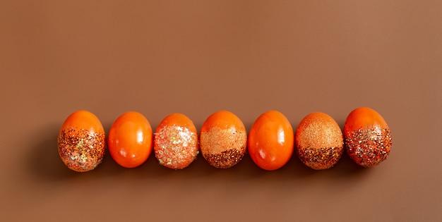 Piękna wielkanoc z pomarańczowymi ozdobnymi jajkami w cekinami.
